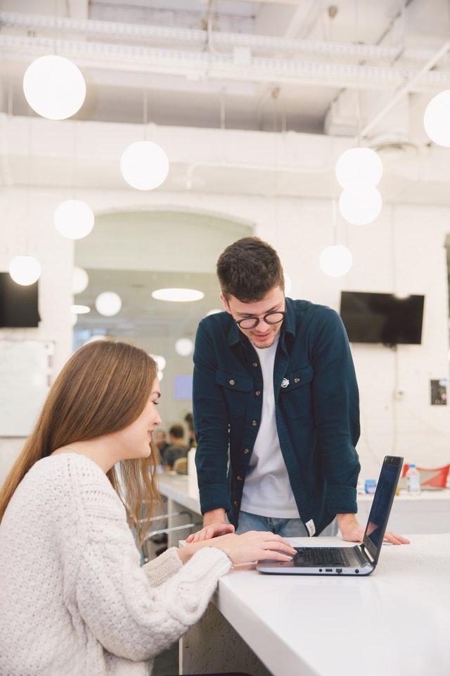 Imagem de mulher ao notebook com homem em pé ao lado