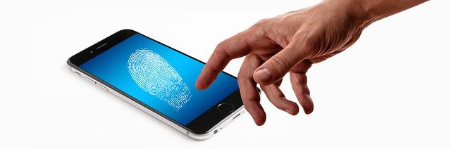 Imagem de celular e mão masculina fazendo a biometria