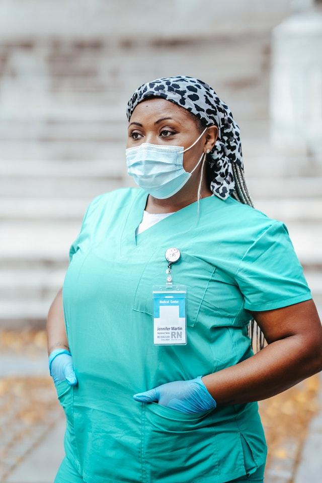 Imagem de enfermeira uniformizada com crachá pendurado em bolso