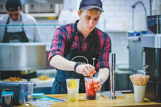 Imagem de homens trabalhando em restaurante. Um com comidas, ao fundo, e outro com as bebidas