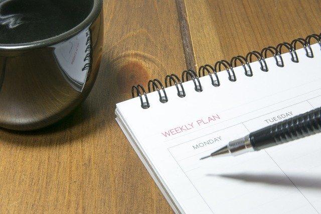 Imagem de pessoa preenchendo plano semanal com lapiseira.